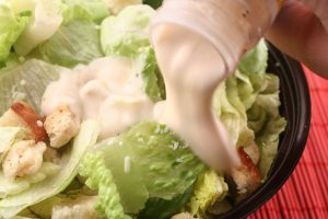 pouring dressing over lettuce for a caesar salad