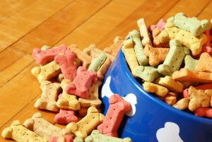 various dog treats and biscuits by a bowl